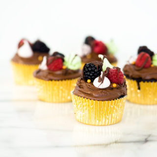 Chocolatey Fudge Cupcake Recipe. Moist, fluffy, pillowy cupcakes in a swirl of fudge chocolate frosting. Decorated in fresh berries and crisp meringues. | thesugarcoatedcottage.com