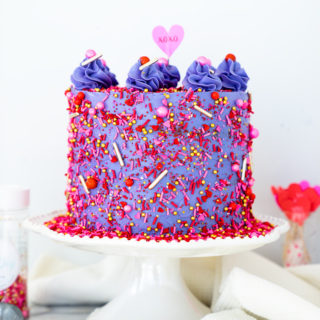 Valentines Red Velvet Cake Recipe. Three layers of southern red velvet cake enrobed in purple swiss meringue buttercream and valentines inspired sprinkles. | thesugarcoatedcottage.com