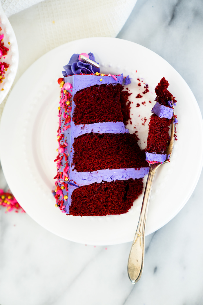 Valentines Red Velvet Cake Recipe. Three layers of southern red velvet cake enrobed in purple swiss meringue buttercream and valentines inspired sprinkles.   thesugarcoatedcottage.com