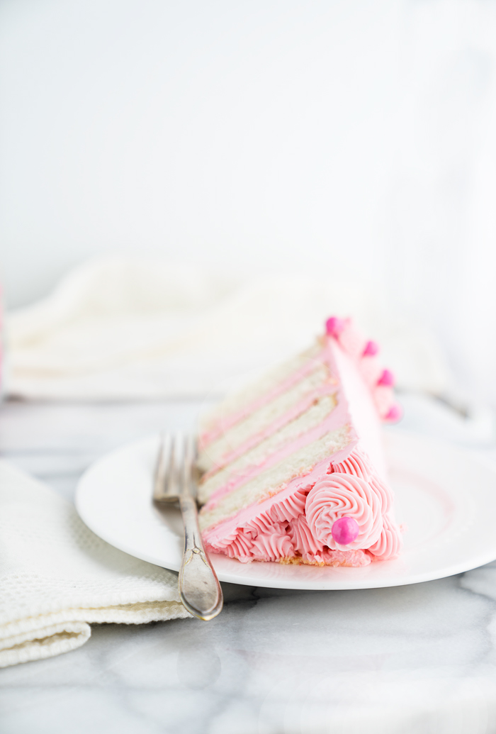 Its a Girl Baby Shower Cake Recipe! White Chocolate Cake coated in a delicate pink white chocolate swiss meringue buttercream. Pink cake, frosting, buttercream, baby shower, cake. | thesugarcoatedcottage.com