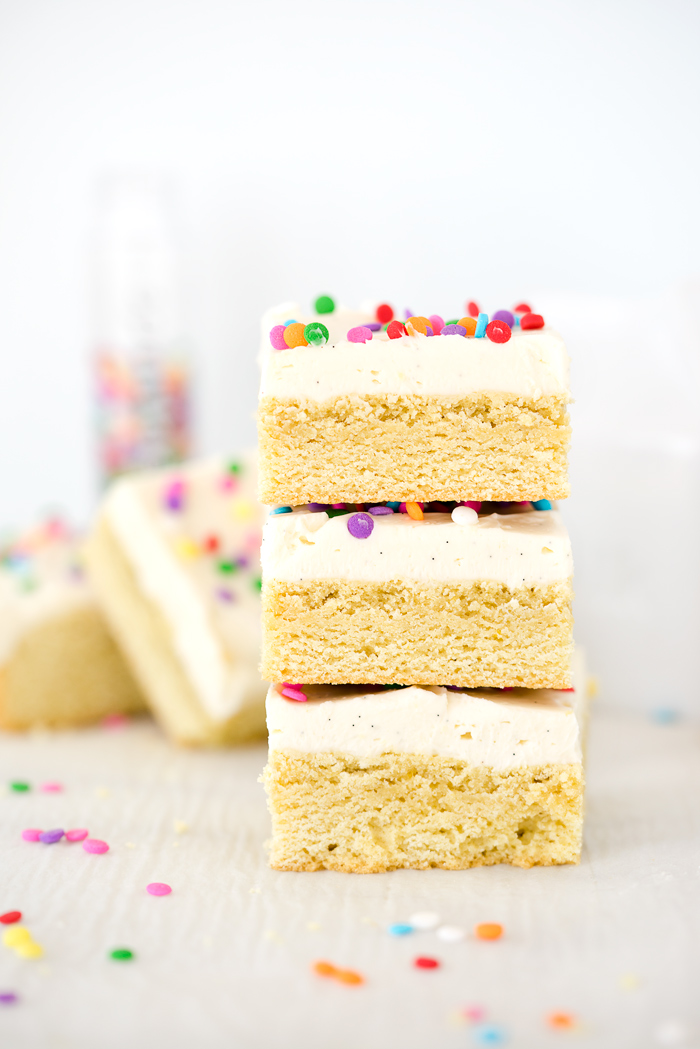 Vanilla Bean Buttercream Frosted Sugar Cookie Bar Recipe. Smooth, creamy vanilla bean flecked swiss meringue buttercream on top of sweet, buttery, sugar cookie bars. | thesugarcoatedcottage.com #recipe #cookies #baking #sugarcookie #buttercream