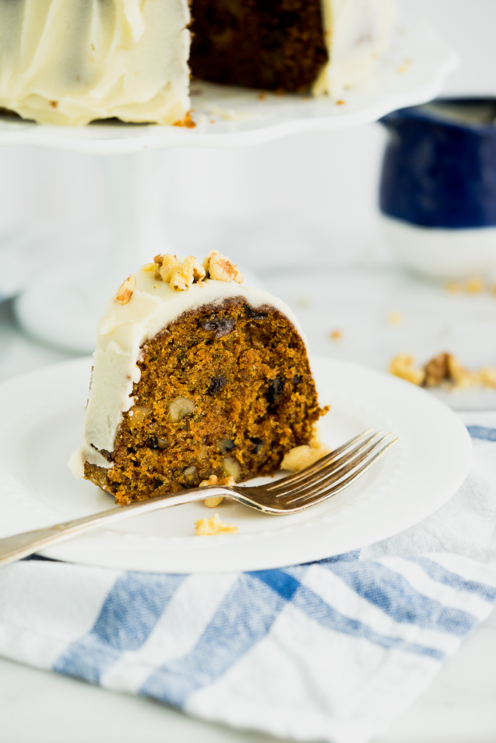 Rum Raisin Carrot Bundt Cake Recipe. Moist, dense, spiced carrot cake with spiced rum soaked raisins and buttery rum icing. The best carrot cake! | thesugarcoatedcottage.com #cake #carrotcake #bundtcake