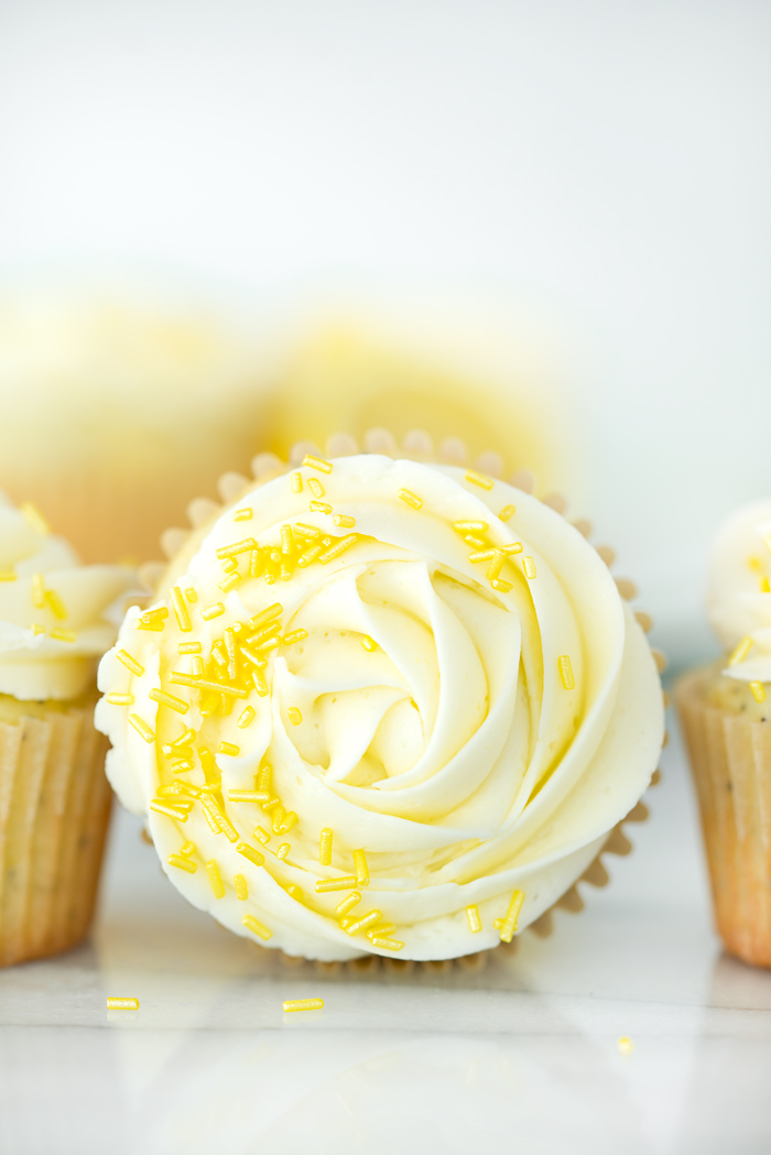 Lemon Poppy Seed Cupcakes. Bright lemony cupcakes speckled with poppy seeds, swirled with lemon buttercream. | thesugarcoatedcottage #cupcake #cake #lemon