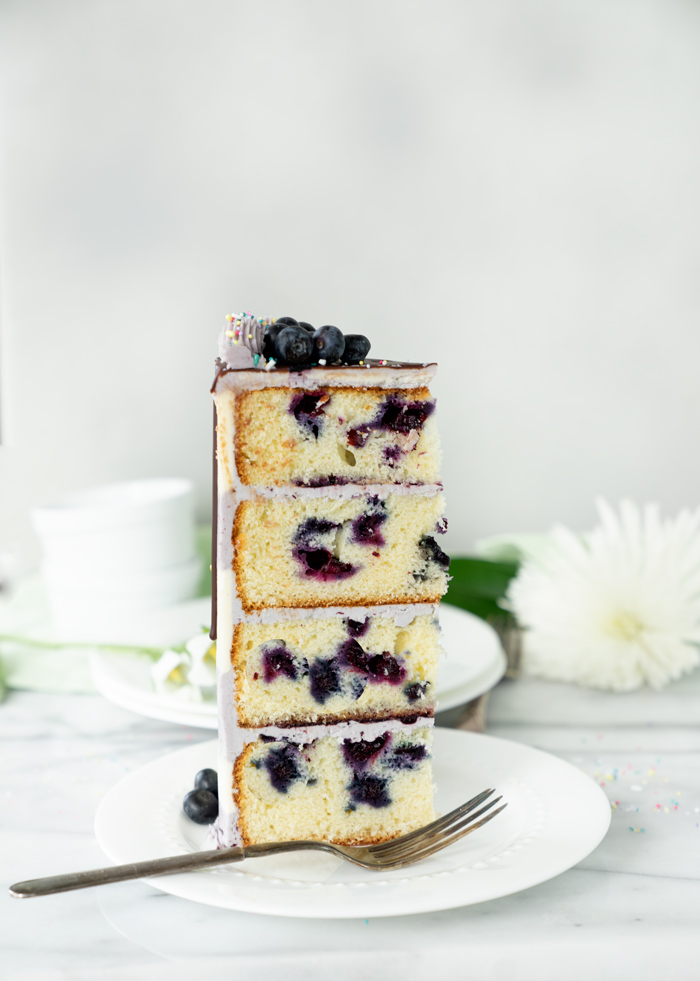 Buttermilk Blueberry Almond Cake Recipe. Blueberry studded cake, hints of almond, blueberry filling all coated in blueberry buttercream! #cake #blueberries