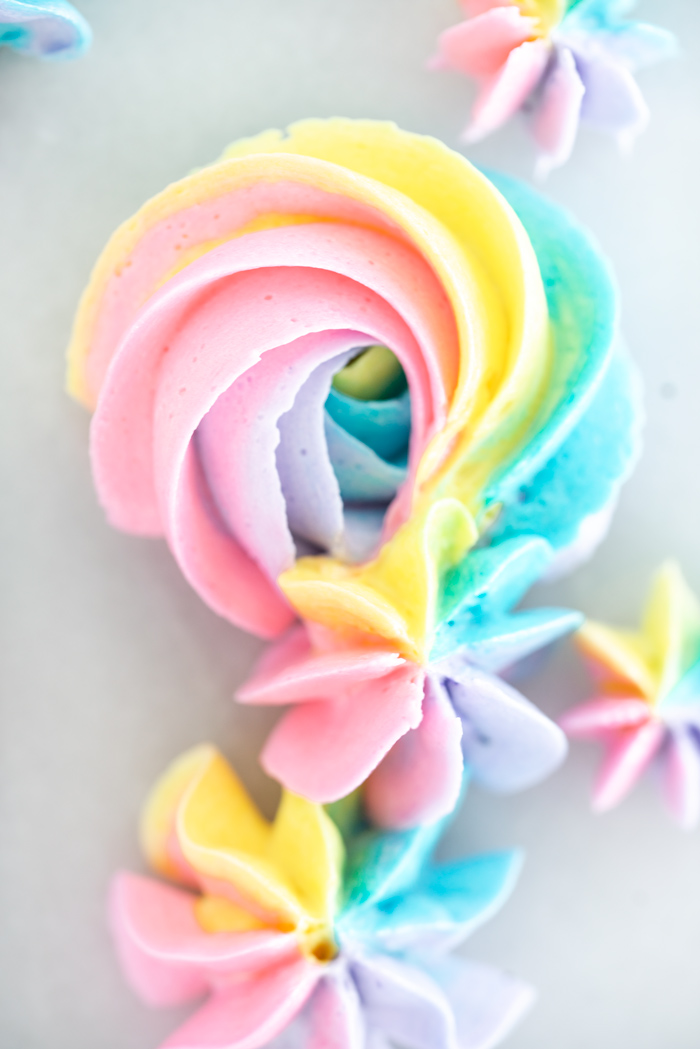 Rainbow buttercream tutorial complete with photos. Now you can make pretty rainbow rosettes and decorations. #cake decorating #cake #buttercreamtutorial