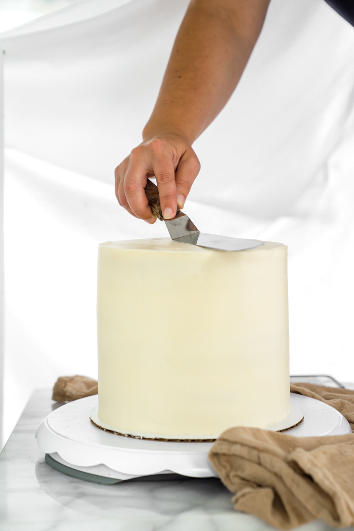 Smooth cake out, dip spatula in warm water/wipe, gently go around cake to smooth out the buttercream appearance.